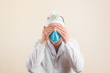 Shocked Doctor With Hands On His Eyes In Protective Medical Mask And White Lab Coat Isolated