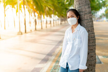 A Young Asian Woman Wearing A White Shirt And Jeans Is Posing For A Photo On The Bangsaen Beach Walkway On A Day When There Are Not Many People Behind The Coconut Trees. Bangsaen, Thailand
