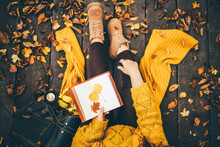 Woman With Yellow Scarf Puts Leaves Between Paper Notebook Pages Sitting On Wooden Bridge In Autumn Forest Close Upper View.