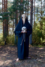A Human Wearing A Plague Doctor Mask Stands And Holds A Human Skull In His Hands