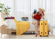 Asian Happy Female Traveler Wear Big Hat Smiling Sitting On Bed Holding Blue Passport Airplane Travel Flight Tickets Leaning On Big Yellow Trolley Luggage In Bedroom Ready For Dream Holiday Road Trip