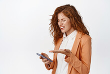 Portrait Of Businesswoman Staring Confused At Mobile Phone, Arguing About Something On Smartphone, Standing Over White Background