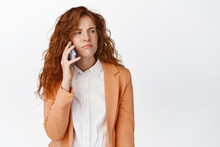 Annoyed Redhead Girl Calling Someone, Waiting For An Answer On Smartphone, Frowning And Grimacing, Standing Over White Background