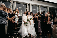 Candid Shot Of Two Female Lesbian LGBT Brides Walking Down The Stairs During Their Wedding Ceremony As Guests Throwing Rose Petal
