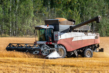 Modern Combine Harvester Working In The Field On A Clear Sunny Day