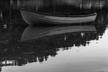 Grayscale Shot Of An Old Boat Reflecting On The Water