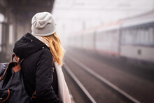 Travel By Train. Woman Waiting For Train On Foggy Railway Station