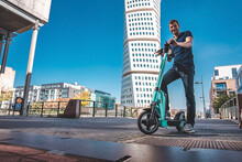 Young Man Riding An Electric Scooter Down The Streets In Malmo. Ecological Transportation Concept.
