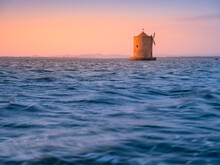 Alone Old Windmill At Sea In Sunset Time With Copy Space In Tuscany In Italy