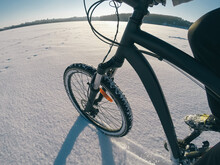 A Young Guy Rides On The Bicycle On Snow Cover Frozen Lake In Winter