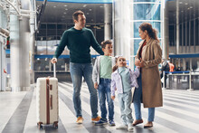 Full Length Of Family With Two Little Kids Waiting For Their Flight At The Airport Terminal