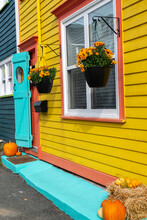 The Front Of A Vintage Building With Yellow Walls, Orange Trim And A Teal Blue Door. There Are Two Pumpkins And Mum Flowers In A Pot Hanging On The Wall. There's A Wooden Shutter Door On The Entrance.