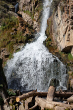 Close-up Of A Powerful Waterfall In High Quality. Side View Of A Sun-drenched Waterfall In The Wild. A Large Stream Of Water Pours Down From The Mountain.