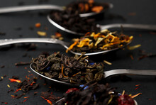 Virious Kinds Of Tea In Tea Spoons On Black Table Close-up, Assortment Of Teas. Black , Green And Fruit Tea, Dry Tea Leaves