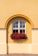 A White Window Placed In An Arch-shaped Recess Against The Background Of A Yellow Wall. A Flower Pot With Red Geraniums On The Window Sill