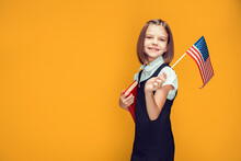 Cute Smiling Caucasian Schoolgirl Holding American Flag And Book On Yellow Background. Flag USA