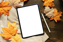 Close Up Top View White  Blank Digital Tablet Screen And Stylus Pen With Group Of Dried Orange Color Maple Leaves On Wood Background Texture Or Autumn Season Collection Design Concept