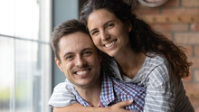 Head Shot Portrait Of Smiling Beautiful Loving Sincere Family Couple Posing Together In Own House. Affectionate Happy Beautiful Millennial Hispanic Woman Cuddling Handsome Man, Looking At Camera.