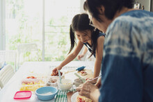 Asian Girl In Casual Dress Having Fun While Make Pizza With Prosciutto, Tomato, Cheese, Vegetables In Home Kitchen. Family And Relationship Concept