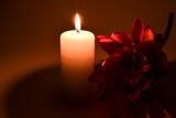Czerwony, sztuczny kwiat i paląca się świeczka.