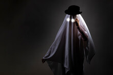 Halloween. The Child Is Covered With A White Sheet, A Ghost. The Drawn Cap.