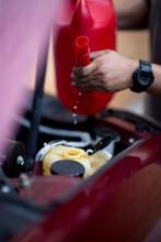 A Mechanic Refills Windscreen Washer Fluid.