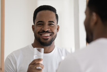 Head Shot Handsome African Guy Reflected In Mirror Smile Look At Camera Holds Glass Of Still Natural Water. Healthy Life Habits, Improve Metabolism, Prevent Dehydration, Control Aqua Balance Concept