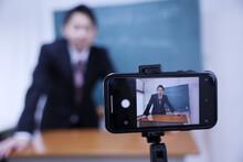 カメラに向かってオンライン授業をするスーツを着た先生