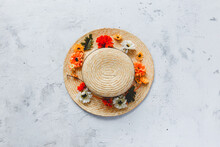 Grey Concrete Flat Lay Background With Colorful Autumn Flower Heads On Straw Hat