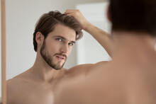 Young Shirtless Guy Looks In Mirror Touch Hair Feels Concerned Due To Receding, Dry, Dull Hair. Hair Loss Common Hair Problem Prevention, Alopecia Treatment Ad, Cosmetics Products For Male Concept