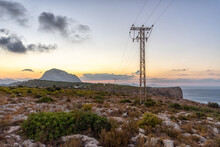 Power Lines In A Mountainous Landscape At Sunset.