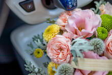 Flower Arrangement In Wicker Basket. Beautiful Bouquet Of Mixed Flowers Placed In A Blue Car Coffee Holder, Near The Gear Shift. Concept: Small Flower Shop, Flowers Delivery.