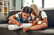 Little Girl With A Broken Leg On The Couch. Two Sisters Draw With Felt-tip Pens On A Plaster Bandage. Children Have Fun And Play On The Living Room Couch.