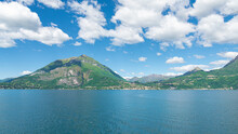 Landscape Of The Coastline Of The Famous Lake Como, Italy, With Turquoise Waters, Green Hills And Italian Alps. In The Distance The Village Of Menaggio Is Visible. Blue Sky And White Clouds.