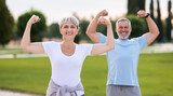 Fit elderly couple flexing arms showing symbol of strength looking at camera broadly smiling