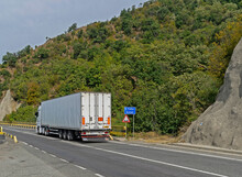 Truck Transporting Goods Moving On A Beautiful Road Near The Mountain. Truck Carrying Various Goods. No Logo Or Brand.