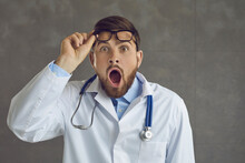 Studio Portrait Of Funny Surprised Doctor. Impressed Young Man In White Lab Coat With Stethoscope Takes Off Glasses And Looks Away With Big Eyes And Shocked, Scared, Amazed, Astonished Face Expression