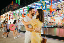 A Young Woman And Her Boyfriend With A Beard Are Dancing Between Amusement Rides