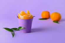 Bucket With Sweet Tangerine Segments On Color Background