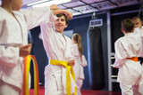 Focused preteen boys practicing new karate moves in pairs at sport gym