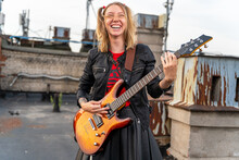 Young Rock Blonde Girl With Tattoos And Two Funny Ponytails, Laughing Loudly And Playing An Electric Guitar On The Roof Of An Old Building, Front View. Musical Video Clip Shooting. Outdoor Show.