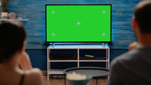 Young Adults Looking At Modern Technology Green Screen On Television At Home. Caucasian People With Copy Space And Virtual Chroma Key For Isolated Template Or Mockup Background