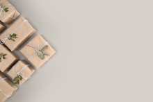 Small Gift Boxes Wrapped In Craft Paper With Dried Eucalyptus Leaves On Solid Gray Background. Modern Minimal Presents Suitable For Any Occasion. Neutral Holiday Backdrop With Copy Space.