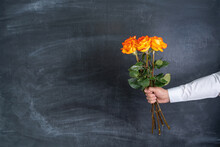 A Man Holds In His Hand Three Orange Roses Against The Background Of A Chalk Board