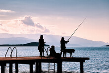 Silhouette Of A Woman Catching Fish With A Fishing Rod On The Pier With Two Other Women And A Dog.