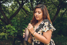 A Gorgeous Plus Size Asian Lady In A Floral Dress Enjoying A Sip From Her Tumbler. Outdoor Scene.