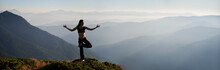 Panoramic View Of Fit Young Woman Performing Yoga Pose On Grassy Hill With Mountains And Sky On Background. Beautiful Woman In Sportswear Practicing Yoga Outdoors. Copy Space.