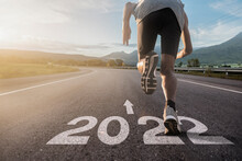 A Runner Runs On A Road Marked 2022. Beginning And Start Of The New Year 2022, Goals And Plans For The Next Year. Happy New Year 2022.