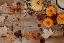 Flat Lay Autumn Background Decoration From Dry Leaves, Straw Hat And Pumpkin On Wooden Background. Top View For Autumn, Fall, Thanksgiving Concept.