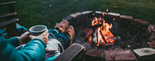 Unrecognizable Woman Enjoying Hot Tea From A Tin Cup In Campsite With Fire Pit. Girl In Folk Blanket By Burning Campfire With Mountain Landscape With Evening Sunset Sky Over The Forest And Hills.